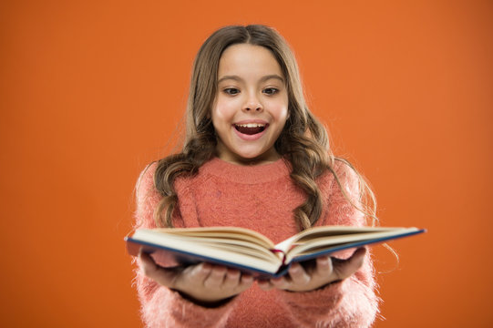 Child enjoy reading book. Book store concept. Wonderful free childrens books available to read. Childrens literature. Reading activities for kids. Girl hold book read story over orange background