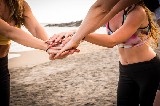 closeup of hands and bodies from three beautiful young girls doing fitness exercises to stay well and enjoy the healthy lifestyle - millennial people in outdoor sport concept all together forever