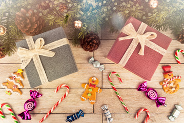 Gift boxes and decoration under Christmas tree, white wooden plank in background, directly above.