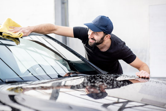 Handsome washer in t-shirt and cap wiping windshield with yellow microfiber at the open air car wash