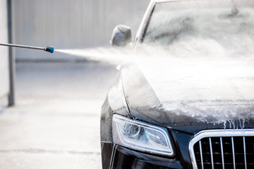 Obraz Close-up of a car under the water jet during the washing process on a self service car wash - fototapety do salonu