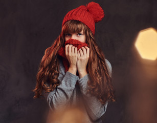 Portrait of a beautiful redhead girl wearing a warm sweater, covers her face with a scarf.