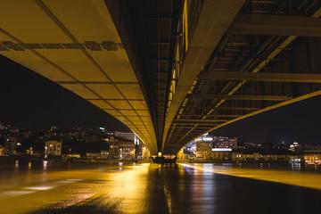 Under bridge with light near river