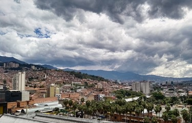 Panoramic view of Medellin in the Aburra Valley (Antioquia, Colombia). Dramatic storm sky, many palm trees and brick buildings.