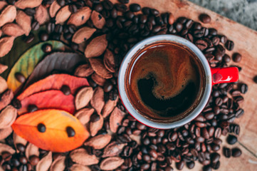Coffee surrounded with autumn leaves on wooden table.