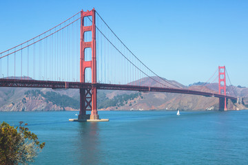 Classic panoramic view of famous Golden Gate Bridge seen from Baker Beach in beautiful summer sunny day with blue sky, San Francisco, California, USA