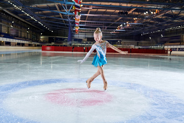 Full length portrait of talented little girl figure skating in indoor rink during performance in spotlight, copy space