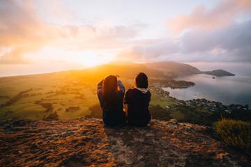 Two female hikers enjoying sunrise overlook