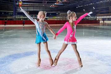Full length portrait of two little girls posing during figure skating performance in spotlight