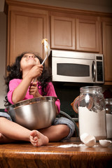 Young girl sitting on counter top with mixing bowl