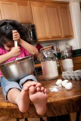 Young girl mixing recipe in mixing bowl