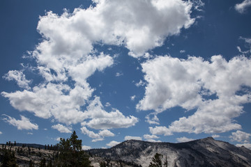 Puffy white clouds over a mountain range