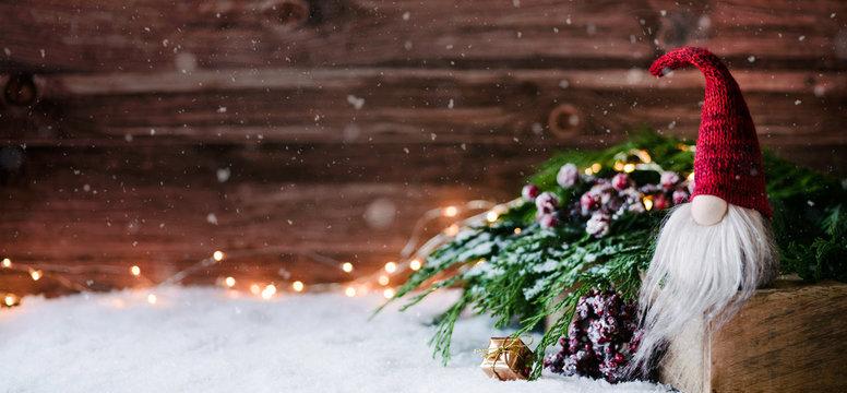Weihnachtswichtel sitzt auf einem Holzbrett in winterlichter Dekoration und wartet auf Weihnachten - Banner, Header, Headline - Format