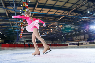 Low angle portrait of teenage girl doing figure skating move during figure skating performance in spotlight, copy space