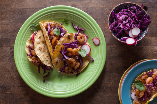 Several shrimp tacos on a green plate with a bowl of cabbage and onions