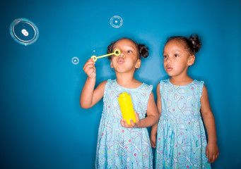 Twin girls blowing bubbles