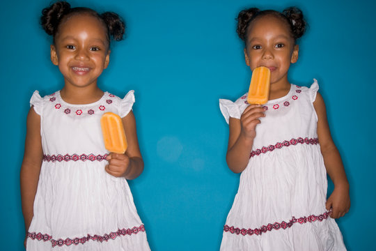 Twin girls eating popsicles