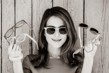 Style adult girl with collection of sunglasses on wooden background. Image in black and white color