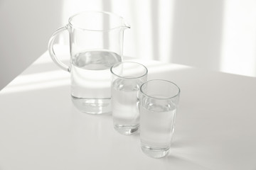 Glassware of fresh water on table against light background