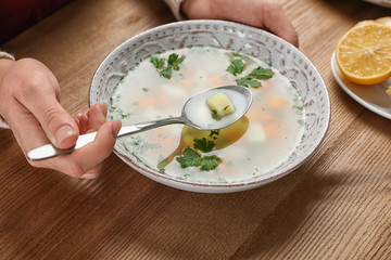 Sick woman eating fresh homemade soup to cure flu at table, closeup
