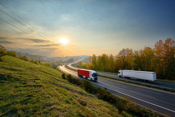 Trucks driving on the asphalt highway in autumn landscape at sunset
