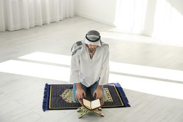 Muslim man with Koran praying on rug indoors