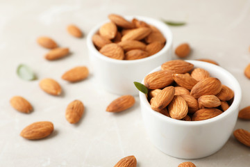 Tasty organic almond nuts in bowls on table. Space for text