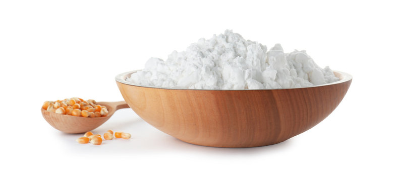 Bowl of corn starch and spoon with kernels on white background