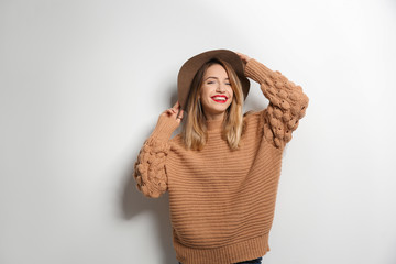 Wall Mural - Beautiful young woman in warm sweater with hat on white background