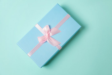 Small gift box wrapped blue paper isolated on pink pastel colorful trendy geometric background. Christmas New Year birthday valentine celebration present romantic concept