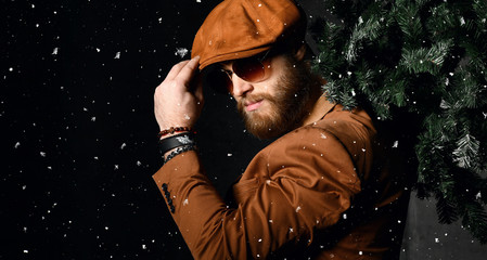 Bearded man in brown leather jacket and cap hold Christmas tree under snow