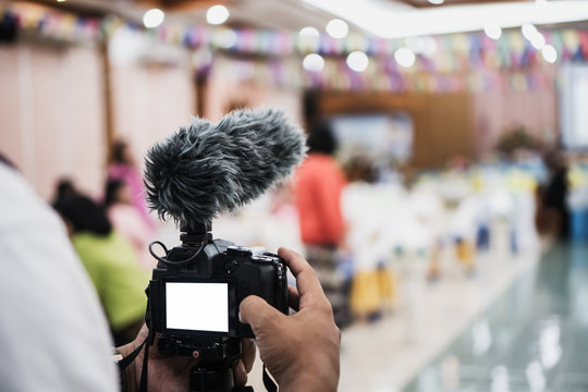 Cameraman Video or professional digital mirrorless on tripod for camera recording with microphone taking photograp in wedding convention hall in live streaming event, seminar production equipment.