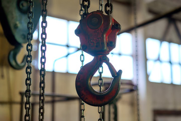 a red hook is hanging on a chain in a heavy lifting room.