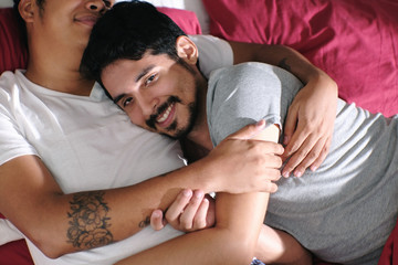 Homosexual Couple Hugging and Relaxing In Bed