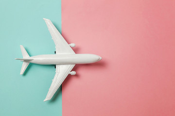 Simply flat lay design miniature toy model plane on blue and pink pastel colorful paper trendy geometric background. Travel by plane vacation summer weekend sea adventure trip concept
