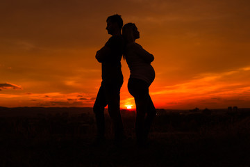 Silhouettes of husband and pregnant wife having conflict while they standing outdoor.