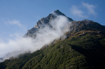 A mountain with a morning mist at the beginning of the Routeburn Great Walk in Fiordland in New Zealand