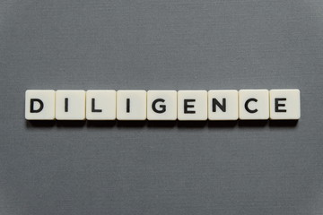 Diligence word made of square letter word on grey background.