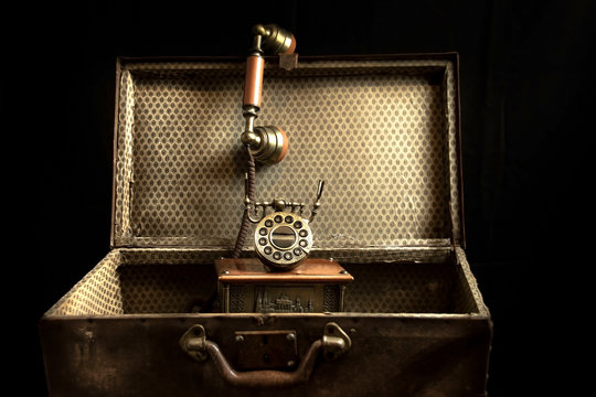 Vintage background. Very old suitcase and telephone isolated on black.