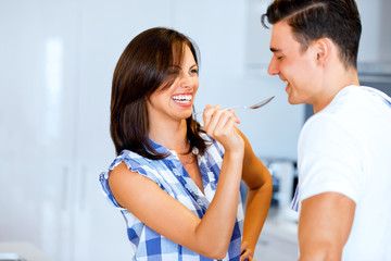 Young couple in the kitchen tasting food