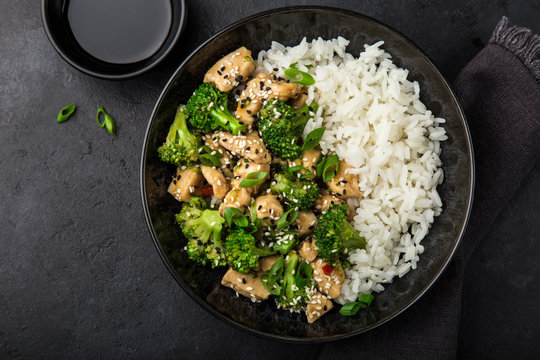 teriyaki chicken and broccoli with steamed rice in bowl