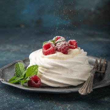mini pavlova  meringue cake with whipped cream and fresh raspberry