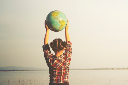 Girl holding globe with nature background