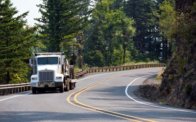 Big rig classic semi truck transporting construction equipment and driving on the winding mountain road