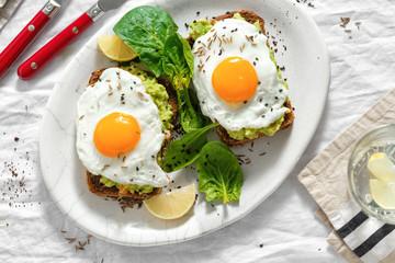 Deurstickers Gebakken Eieren Top view healthy avocado toasts breakfast lunch fried eggs white background lemon water
