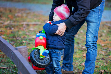 Preschool child with father having fun with tricycle outdoor