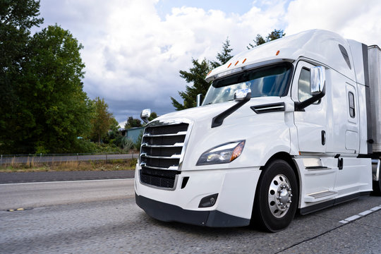 Comfortable white modern big rig semi truck running on divided highway