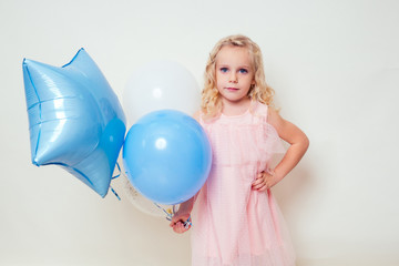 cute little girl holding helium blue, yellow and gold balloons on white background in studio