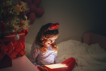 Happy little child girl holding a magical Christmas box with a gift