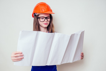 Teenager girl with plan holding urban designer paper in a construction helmet hard hat and glasses